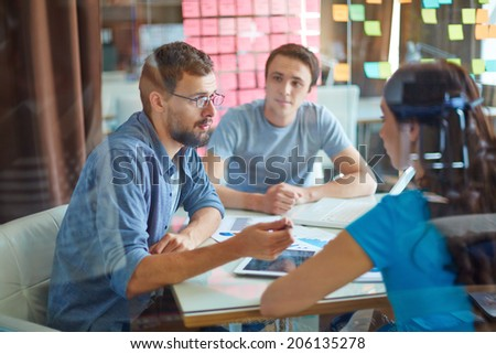 Young man consulting his business partner at meeting in office
