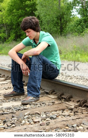 Young Man Contemplating Life on Train Tracks