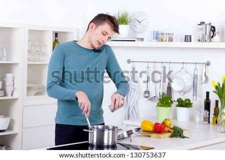 young man cooking a meal and talking on the phone in his kitchen