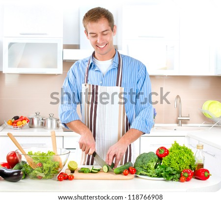 Young Man Cooking. Healthy Food - Vegetable Salad. Diet. Dieting Concept. Healthy Lifestyle. Cooking At Home. Prepare Food - stock photo