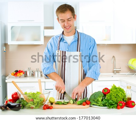 Young Man Cooking in the kitchen. Healthy Food - Vegetable Salad. Diet. Dieting Concept. Healthy Lifestyle. Cooking At Home. Prepare Food  - stock photo
