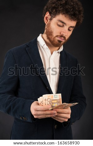 Young man counting euros banknotes against black background. - stock photo