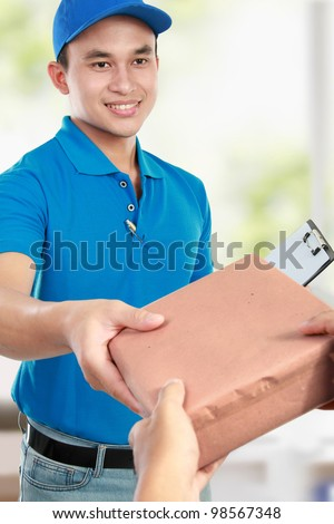 Young man courier in blue uniform giving the packages - stock photo