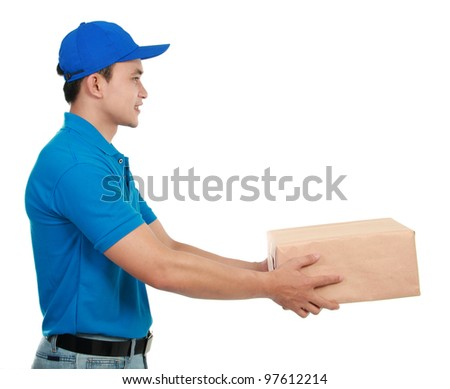Young man courier in blue uniform stretching out his hand to give the packages - stock photo