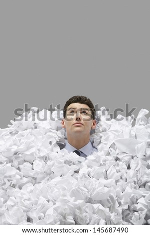 Young man covered in crumpled papers looking up against gray background - stock photo