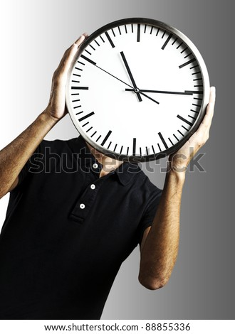 young man covering his face with a clock over grey background