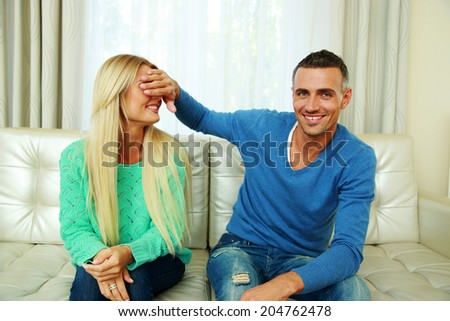 Young man covering his girlfriend`s eyes - stock photo
