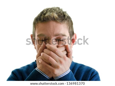 Young man covering his mouth with hands, trying not to laugh