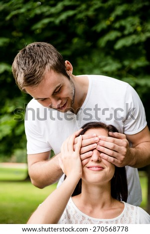 Young man covering with hands eyes of young beautiful woman - outdoor - stock photo