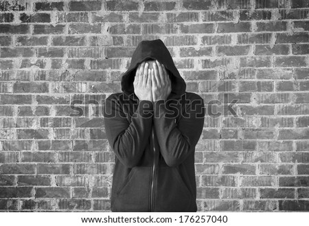 young man covers his face with hands with bricks wall as background,black and white