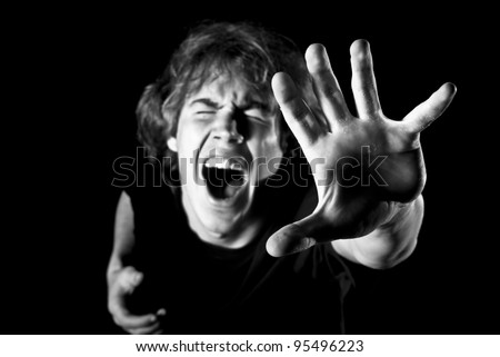 Young man cries out in pain and reaches up - stock photo