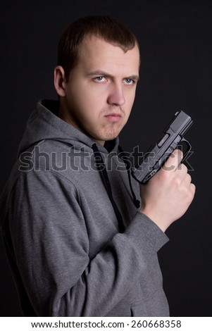 young man criminal holding gun over grey background - stock photo