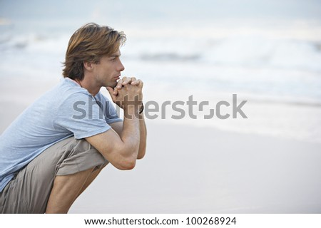 Young man crouching by the sea shore looking at sea, thoughtful. - stock photo