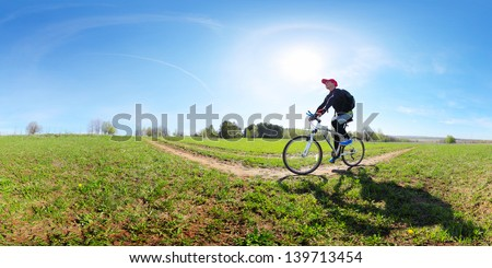 Young man cycling on a rural road through green spring meadow at sunny day