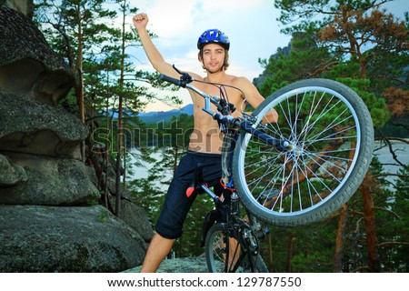 Young man cyclist holding his bicycle on the top of a hill.