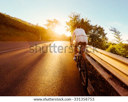 Young man Cyclist on road bike in sunset. Cycling