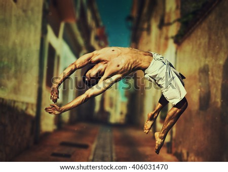 Young man dancer jumping on old town street background - stock photo