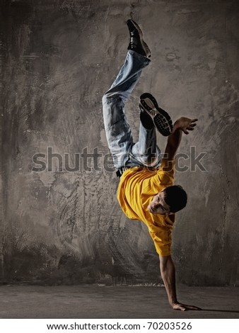 Young man dancing against grunge wall