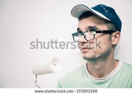 Young man decorating interior with paint roller. - stock photo