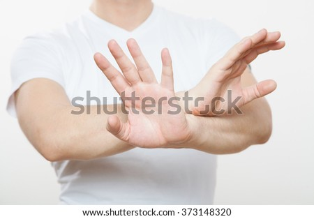 Young man demonstrating prohibiting of a gesture, white background