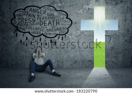 Young man desperate sitting on the floor with a cross symbolizing jesus next to him - stock photo