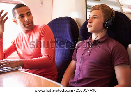 Young Man Disturbing Train Passengers With Loud Music - stock photo