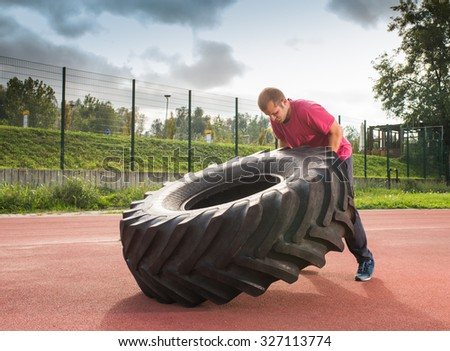 Young man does strongman exercise