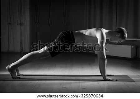 young man does yoga in sports hall - stock photo