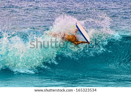 Young man doing a barrel roll while boogie boarding on Maui, Hawaii, USA - stock photo