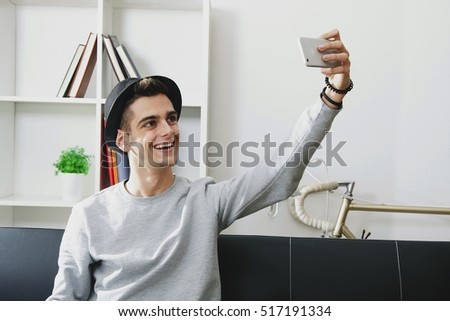 young man doing a selfie at home with mobile phone