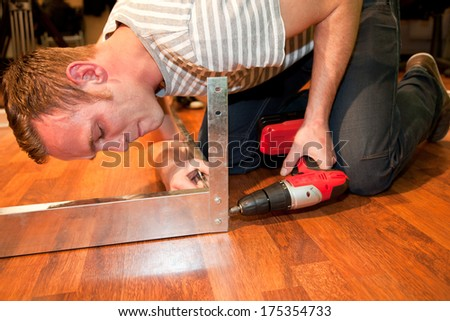 Young man doing DIY home improvements bending down on a wooden floor drilling a hole into a metal bracket