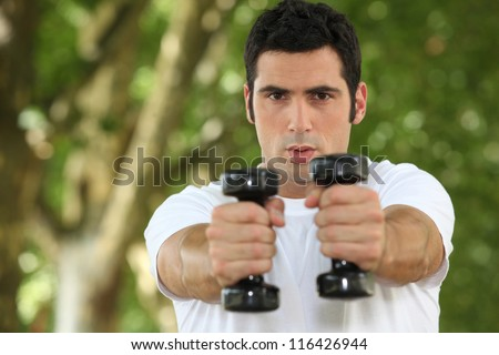 young man doing fitness in a park - stock photo