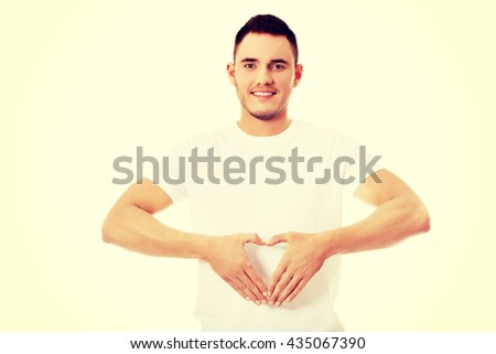 Young man doing heart gesture - stock photo