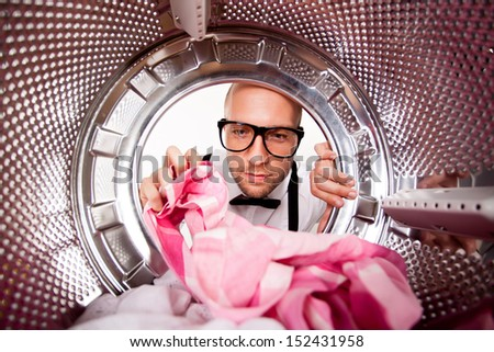 Young man doing laundry View from the inside of washing machine.  - stock photo