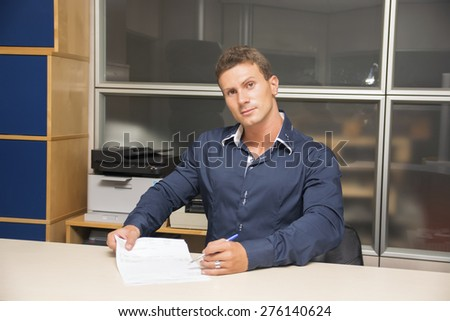 Young man doing paperwork at office desk, writing on a document and asking for signature - stock photo