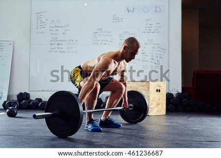 Young man doing power snatch exercise at gym during weightlifting workout