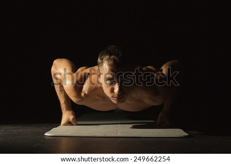 Young man doing push ups isolated on black background  - stock photo
