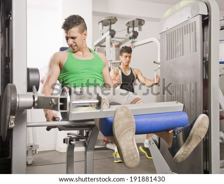Young man doing quadriceps exercises Man in background training pecs - stock photo