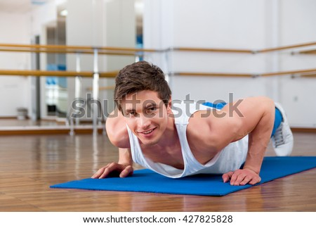 Young man doing sit ups in the fitness studio - stock photo