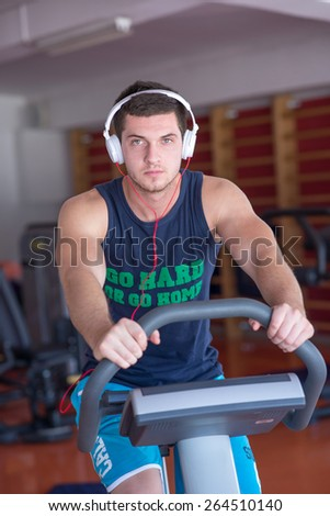 young man doing sport spinning with headset in the gym - stock photo