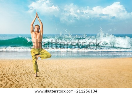 Young man doing yoga and meditating in tree position at sea beach - stock photo
