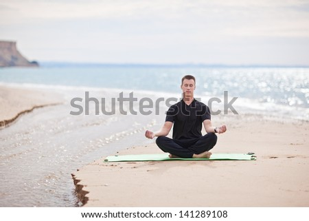young man doing yoga on the beach - stock photo