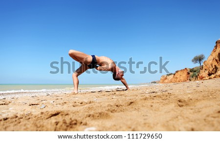 Young man doing yoga pose at the deserted sea beach - stock photo