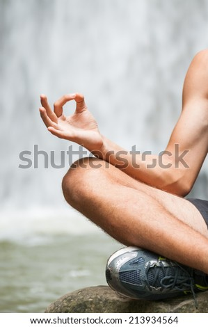 Young man doing yoga with waterfall in the background. Having a healthy lifestyle. Zen meditation and Spa concept - stock photo