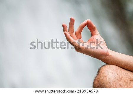 Young man doing yoga with waterfall in the background healthy lifestyle. Zen meditation and Spa concept - stock photo