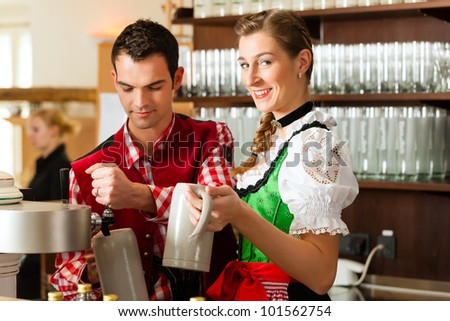 Young man drawing beer in restaurant or pub, he is the innkeeper - stock photo
