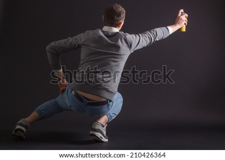 Young man draws your can graffiti sitting back - stock photo
