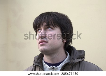 Young man dreaming outdoor. Solid pastel background  - stock photo