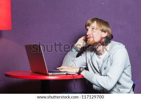 Young man dreaming with laptop in cool  location