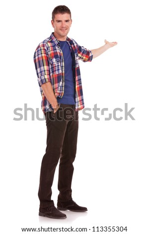 Young man dressed casual is presenting something while holding his other hand in his pocket. - stock photo